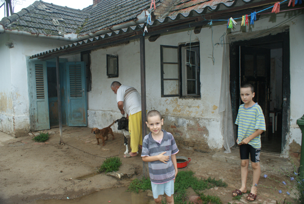 Régi, rossz állapotú ház, előtte szegény előtte egy férfi állatot etet és két kisfiú rongyos ruhában