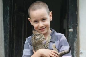 Kidfiú egy kisciát tart a kezében