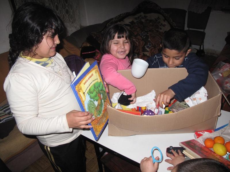 Gyerekek bontják ki az ajándékcsomagot, benne sok-sok játék.