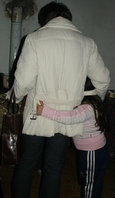 Egy kislány átkarolja édesanyja lábát