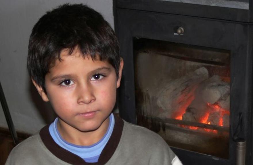 Egy kisfiú a kandalló előtt. Szerényen öltözött szép szemek.